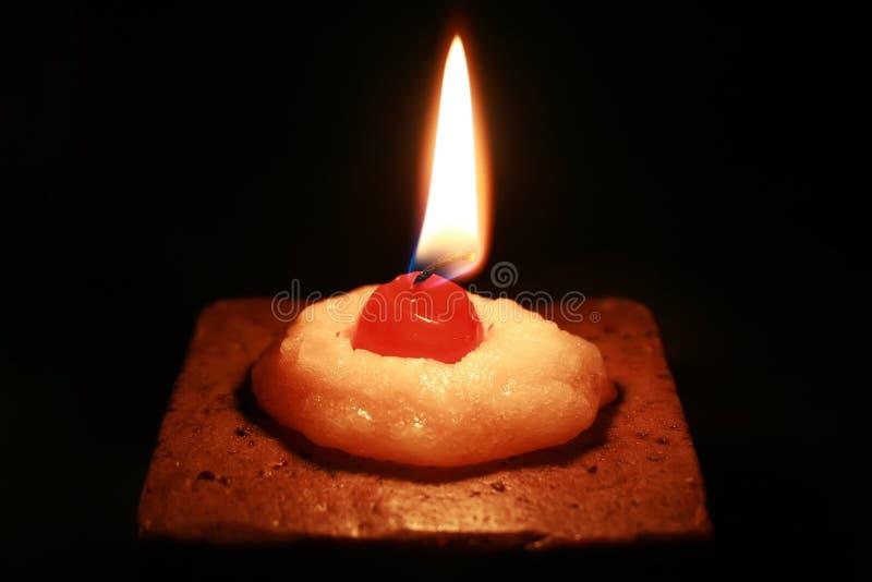 Une bougie en forme de gâteau brûlante avec une cerise de cire sur le dessus images stock