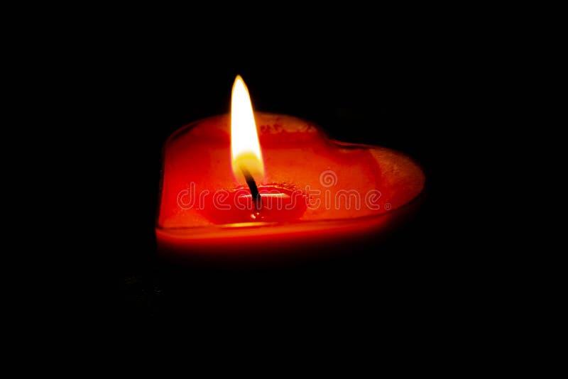Une bougie rouge d'amour montrée sur un fond noir images stock