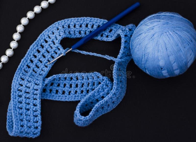 Une boule de fil bleu avec un crochet sur un fond noir photographie stock