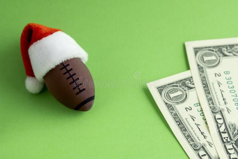Une boule de rugby ou de football américain de souvenir dans un chapeau rouge de Santa Claus à côté de deux dollars sur un fond v photo libre de droits