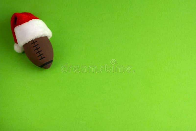 Une boule de souvenir pour le rugby ou le football américain dans un chapeau rouge du père noël sur un fond vert Préparation pour image stock