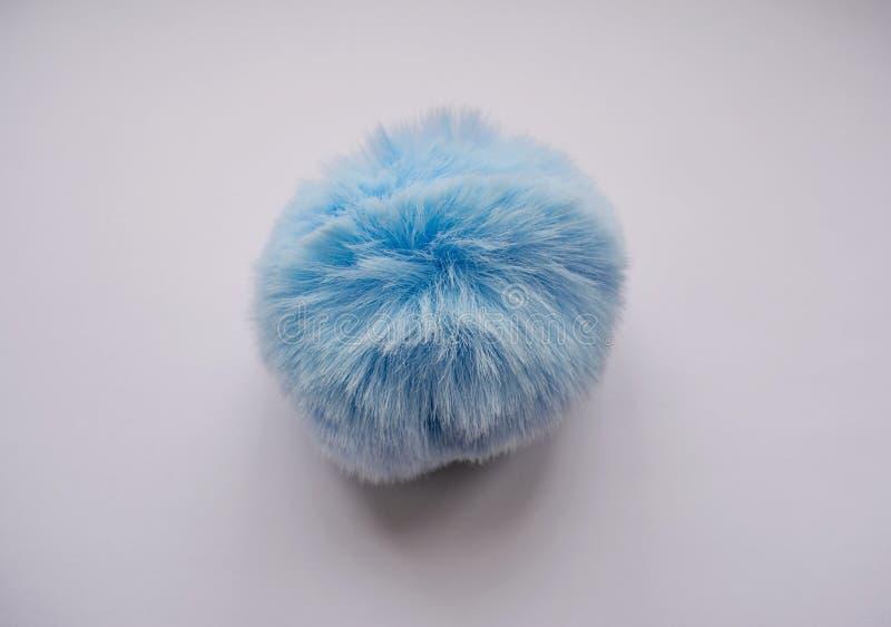 Une boule ronde, sphérique, pelucheuse, bleue, molle est un jouet photos stock