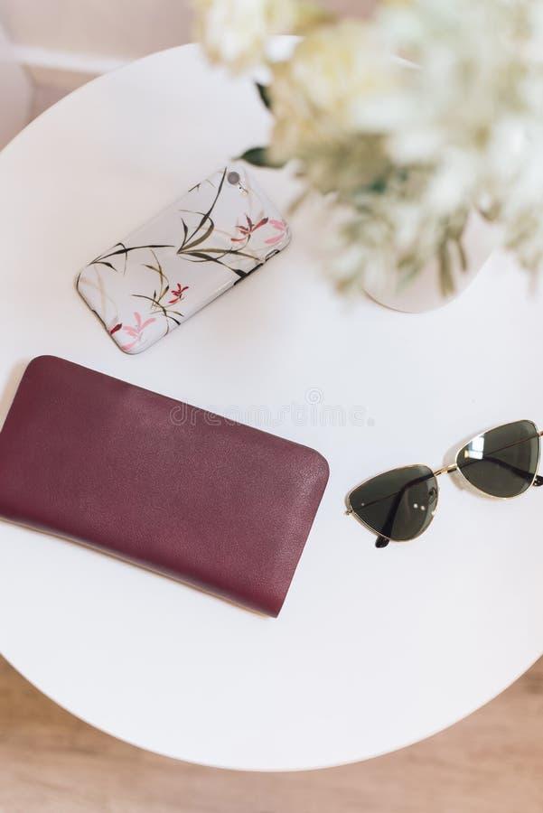 Une bourse de Bourgogne, lunettes de soleil avec les verres foncés et un mensonge de cas de téléphone sur une table ronde blanche photos stock
