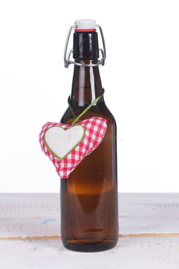 Une bouteille à bière avec le coeur sur la terre en bois image stock