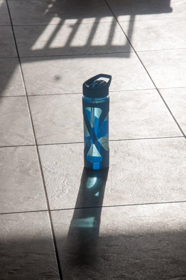 Une bouteille d'eau simple avec l'ombre sur le plancher photos stock