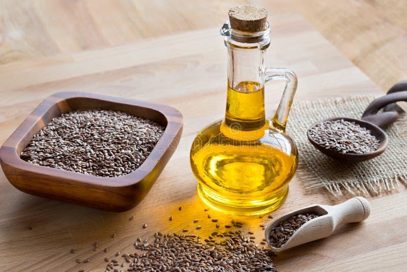 Une bouteille d'huile de semence d'oeillette, avec des graines de lin à l'arrière-plan photos stock