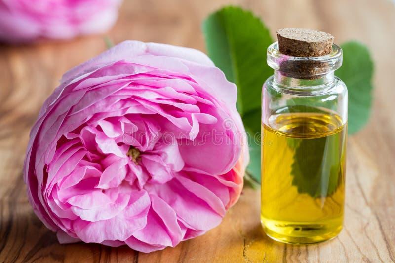 Une bouteille d'huile essentielle avec une fleur de rose photos stock