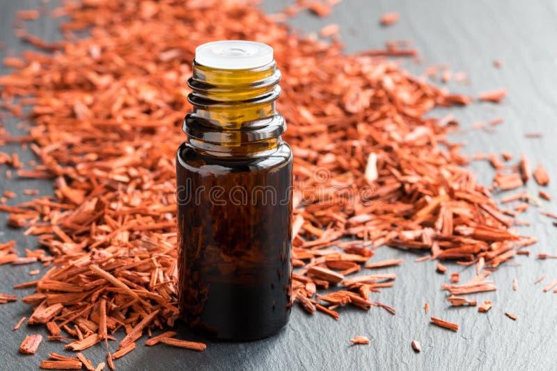 Une bouteille d'huile essentielle de bois de santal avec le bois de santal sur un b gris images libres de droits