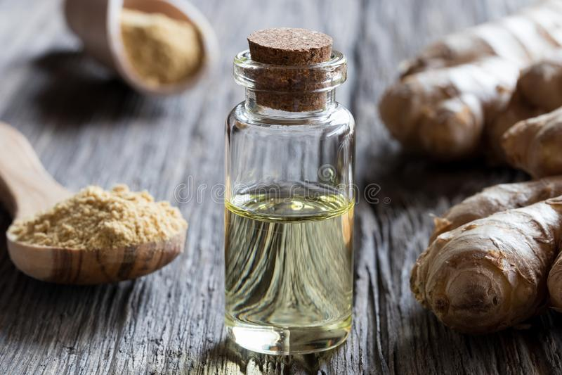 Une bouteille d'huile essentielle de gingembre avec du gingembre frais et sec photos libres de droits