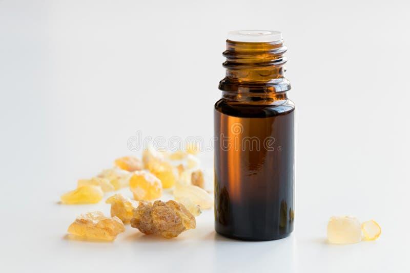 Une bouteille d'huile essentielle d'encens avec l'encens sur le petit morceau photos libres de droits