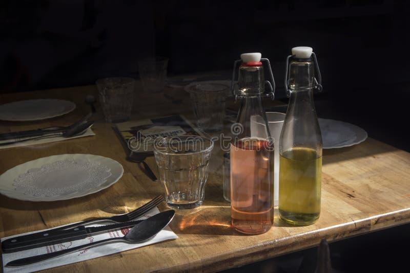Une bouteille d'huile et de vinaigre d'olive est au sujet d'une serviette et d'une fourchette avec un couteau sur une table d'ens photographie stock