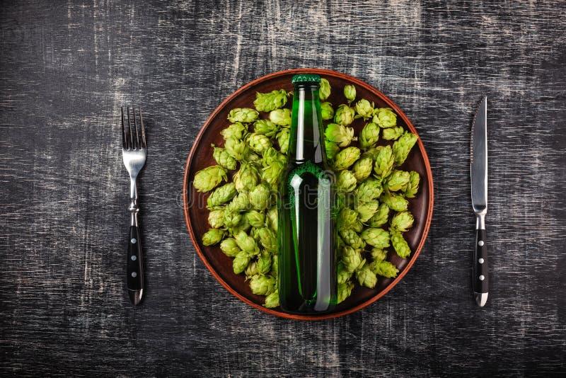 Une bouteille de bière sur un houblon frais vert dans un plat avec le couteau et de fourchette dans la perspective d'un tableau r images stock