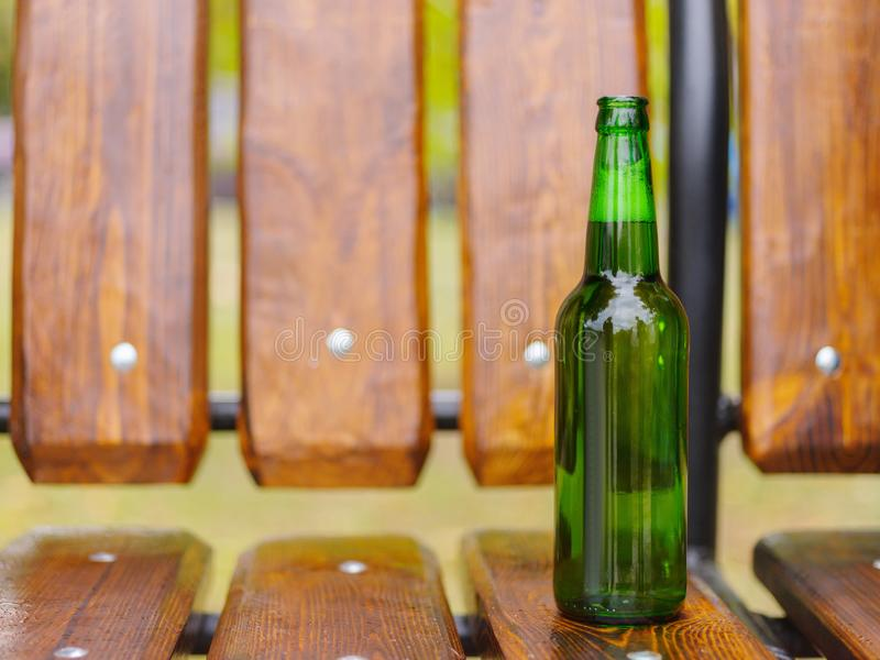 Une bouteille de bière verte se tient sur un banc dans la rue photos stock