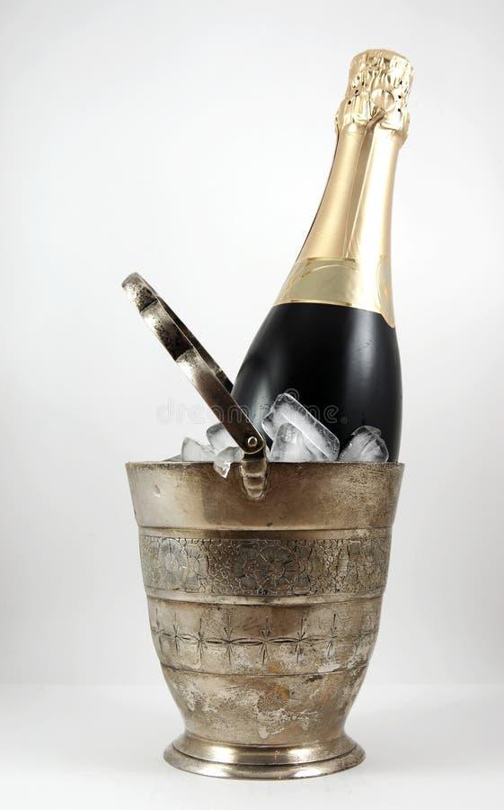 Une bouteille de champagne dans un seau à glace d'isolement image libre de droits