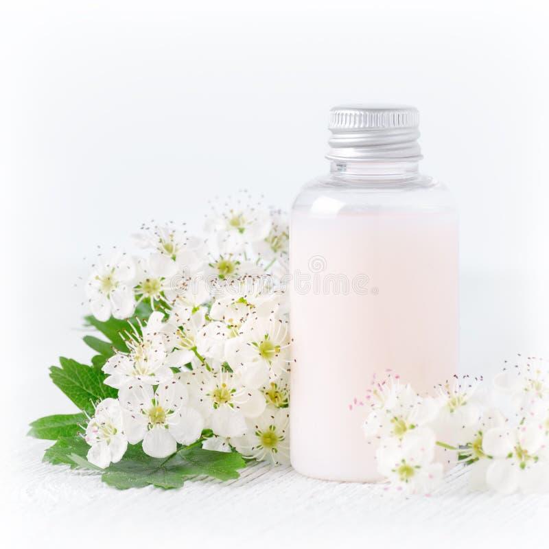 Une bouteille de cosmétique naturel de bébé avec des fleurs image libre de droits