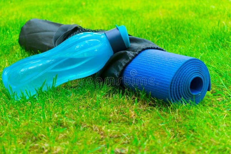 Une bouteille de l'eau sur un tapis de yoga sur l'herbe verte fraîche Le concept des sports et de la r?cr?ation Style de vie sain images stock