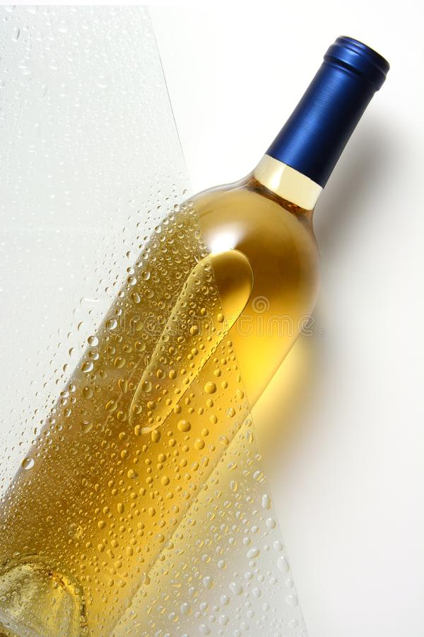 Une bouteille de vin blanc derrière une feuille de verre avec de l'eau se laisse tomber images libres de droits