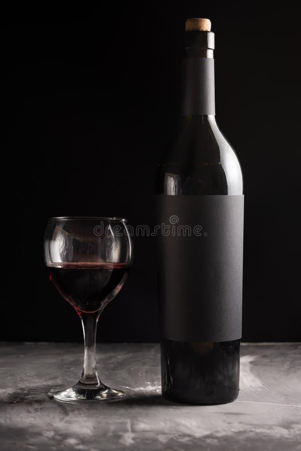 Une bouteille de vin cher rouge avec un label vide noir sur un fond foncé avec un verre de vin rouge photos stock
