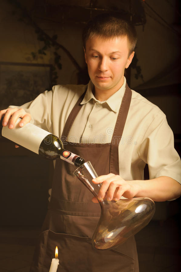 Une bouteille de vin d'ouverture de sommelier photographie stock libre de droits