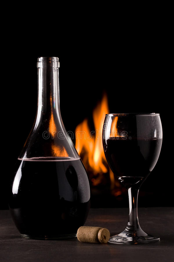 Une bouteille de vin rouge et d'un verre devant une cheminée photographie stock libre de droits