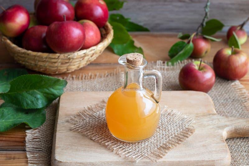 Une bouteille de vinaigre de cidre non filtré cru de pomme avec les pommes fraîches photos libres de droits