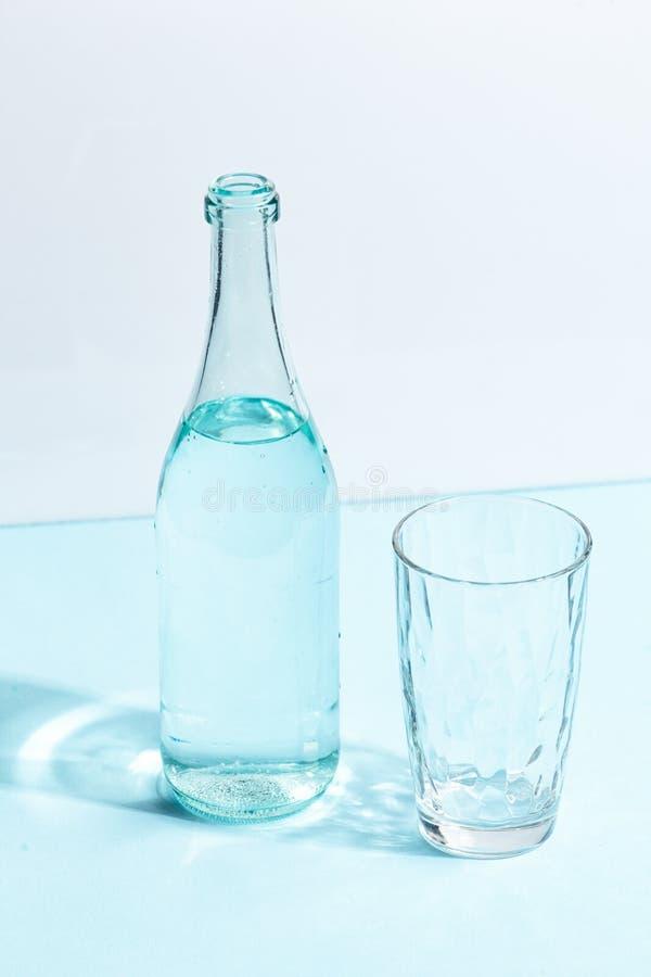 Une bouteille en verre avec l'eau claire et un verre sur un fond blanc-bleu Concept cr?atif de Minimalistic photos stock