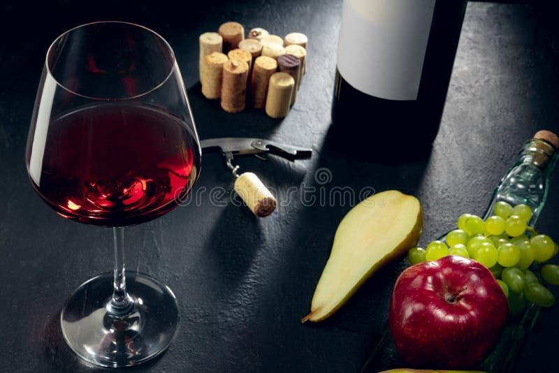 Une bouteille et un verre de vin rouge avec des fruits au-dessus de fond en pierre fonc? photo stock