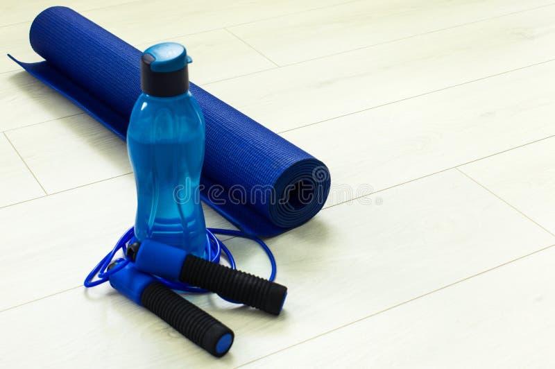 Une bouteille ou une eau à côté d'une corde de saut sur un tapis de yoga photo libre de droits