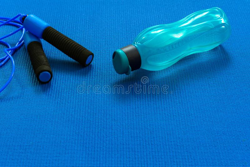 Une bouteille ou une eau ? c?t? d'une corde de saut sur un tapis de yoga Le concept de la formation et du repos photo libre de droits