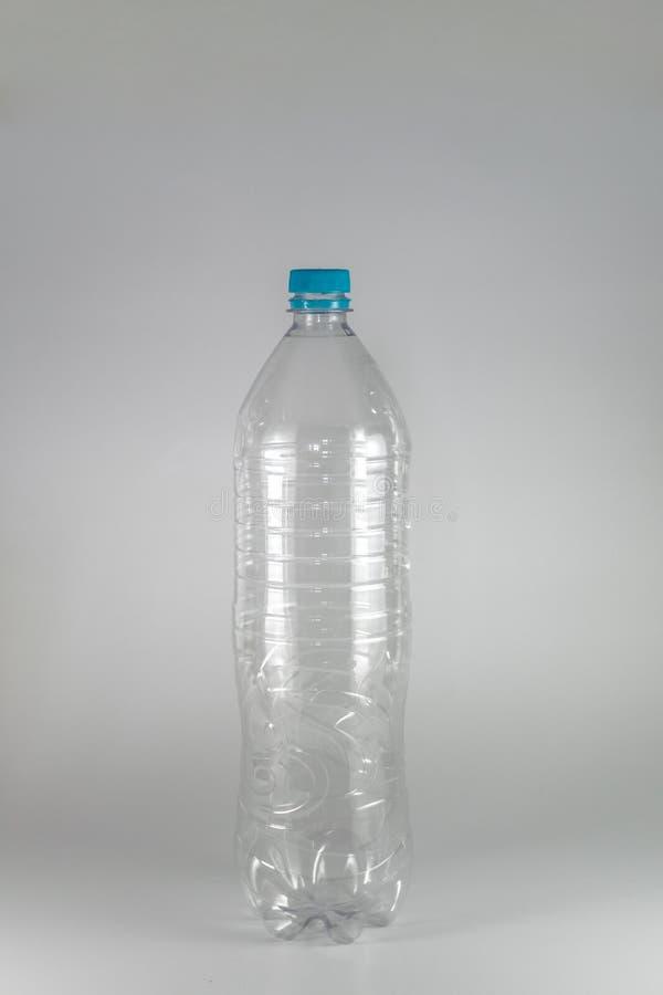 Une bouteille vide d'un litre et d'une moitié de l'eau minérale avec le chapeau bleu et la bague d'étoupage sur un fond blanc, et image stock