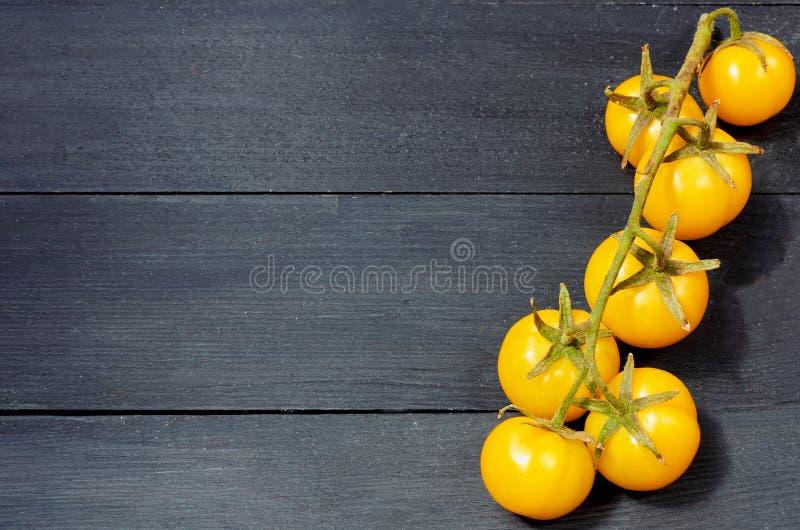 Une branche des tomates-cerises jaunes d'isolement sur le fond en bois noir avec l'espace de copie pour le texte image stock