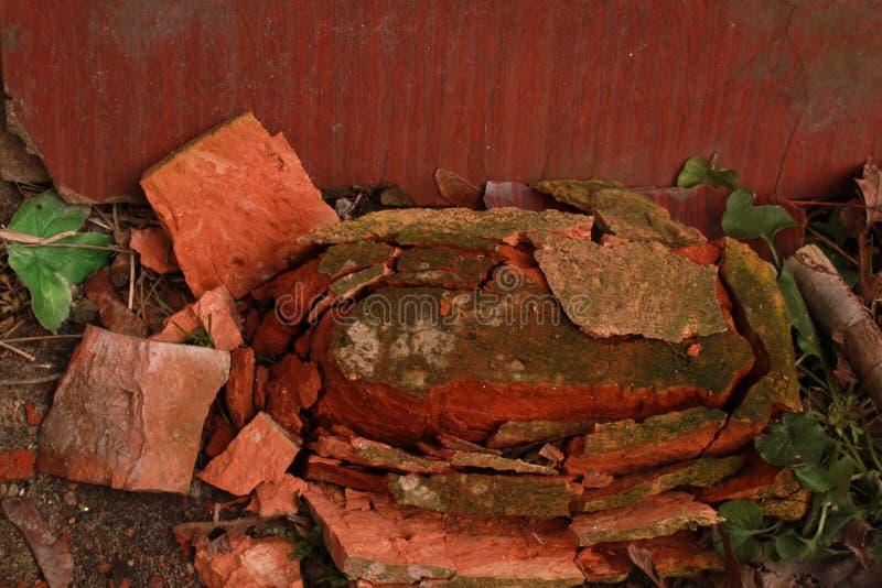 Une brique rouge cassée lèche la terre images stock
