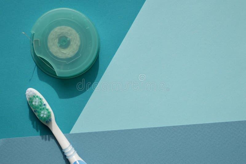 Une brosse à dents et un fil dentaire sur le fond bleu de différents tons Combinaison de blanc, de bleu et de turquoise photo libre de droits