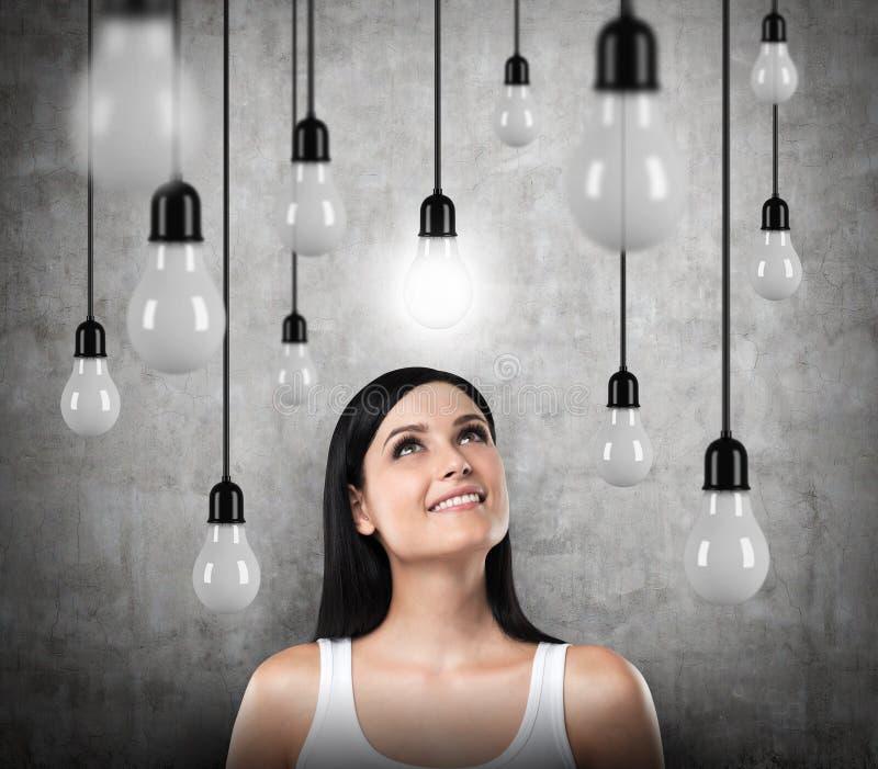 Une brune rêveuse regarde vers le haut Un bon nombre d'ampoules, l'une d'entre elles est allumés photo stock