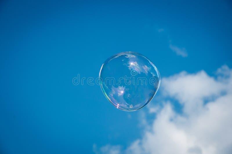 Une bulle de savon ronde sur le ciel bleu image stock