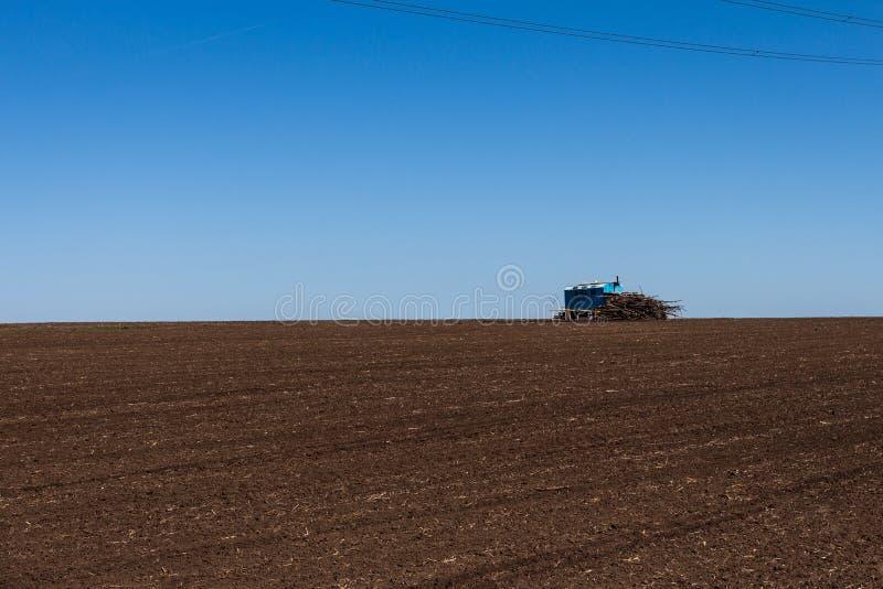 Une cabine isolée contre le ciel et un champ labouré Horizon doux Bleu et brun photos libres de droits