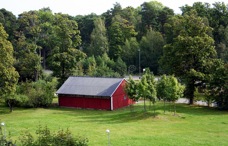 Une cabine rouge parmi les bois image stock