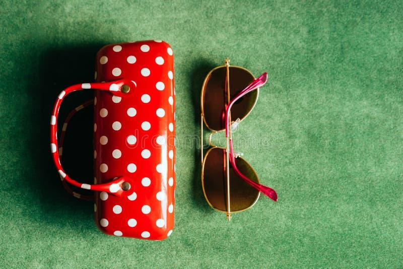 Une caisse femelle à pois blanche rouge en verre et des lunettes de soleil roses photographie stock