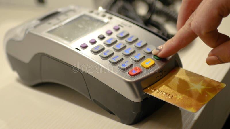 Une caissière de fille utilise un terminal de banque pour effectuer une vente dans le magasin, conduit une carte par le dispositi photographie stock