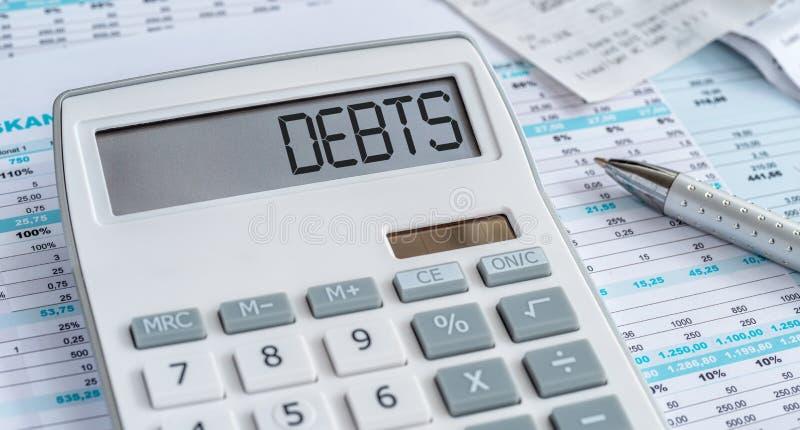 Une calculatrice avec les dettes de mot sur l'affichage photo stock