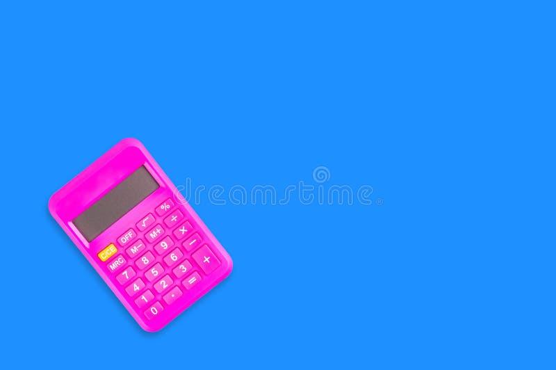 Une calculatrice en plastique rose numérique sur la table bleue dans le bureau copiez l'espace pour votre texte Vue supérieure photos stock