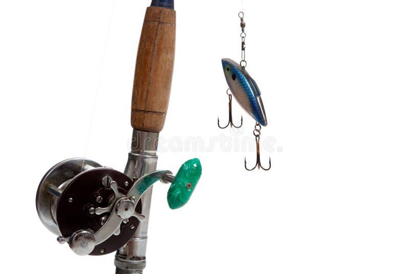 Une canne à pêche, une bobine et un attrait sur un fond blanc photos stock
