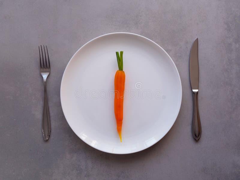 Une carotte cuite d'un plat blanc photos stock