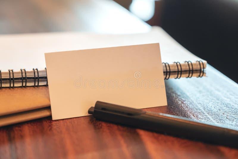 Une carte de visite professionnelle vierge blanche de visite avec des carnets et stylo sur la table en bois de vintage image libre de droits