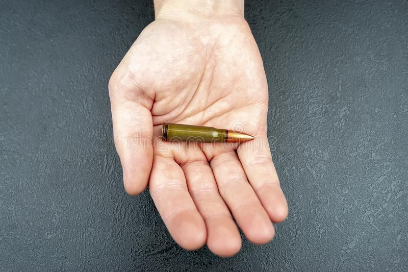 Une cartouche verte pour un fusil d'assaut de kalachnikov se situant dans la main d'un homme photos libres de droits