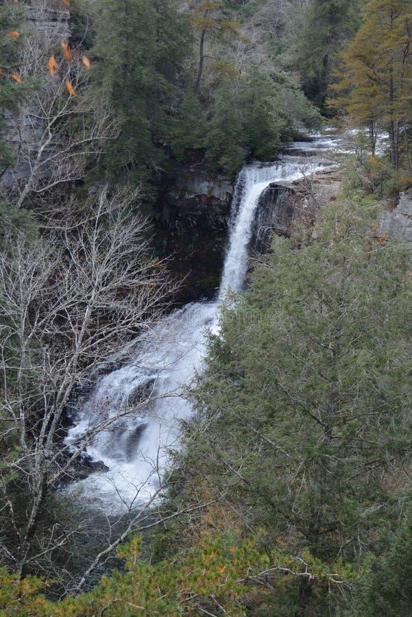 Une cascade coule rapidement au-dessus des roches de lit de la rivière et dans l'étang ci-dessous image stock