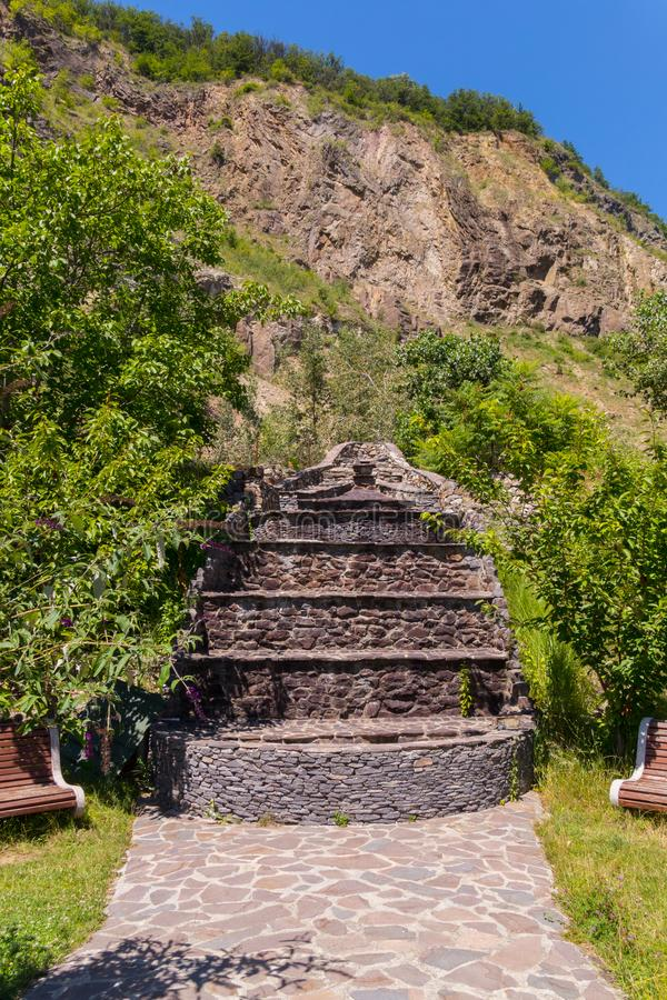 Une cascade de cascade couverte de pierre au pied de la roche et du banc à la nuance de l'arbre images stock