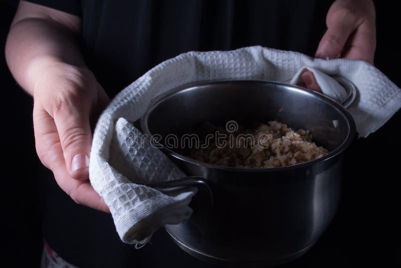 Une casserole avec du sarrasin bouilli avec les champignons et l'oignon dans un woman& x27 ; photos stock