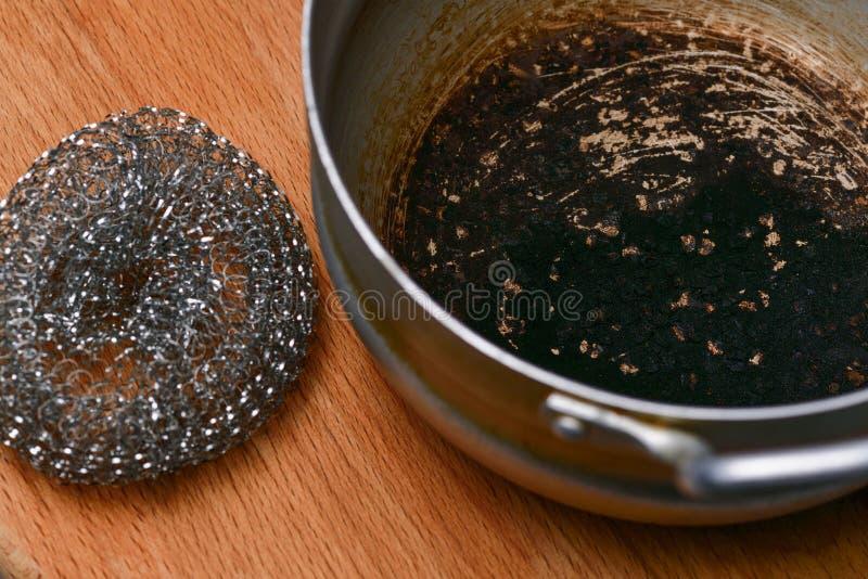 Une casserole brûlée corrompue avec une brosse dure en métal se trouve sur un conseil en bois photo stock