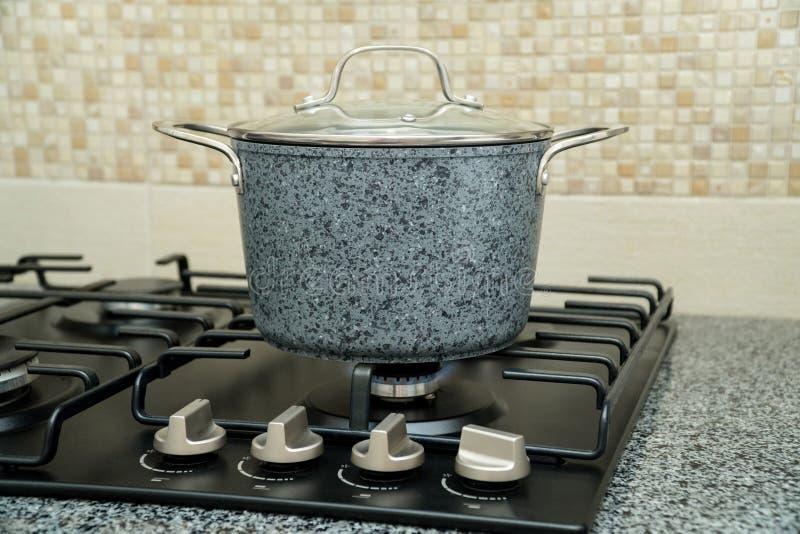 Une casserole moyenne sur une cuisinière à gaz noire photo libre de droits